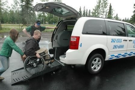 photo of a person assisting a patron using a wheel chair into an accessible van